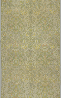 Vertically symmetrical design of elaborate plant forms with detailed fillings in lace-like pattern. Soft shades of ivory, green, yellow, blue, pink. orange and tan.