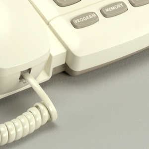 White telephone with spiral cord. Slanted base with large grey buttons. Large emergency buttons at the top. Left side, handset.