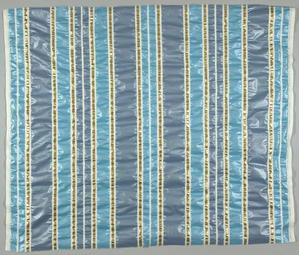 Vertical stripes of varying width in two shades of blue and gold on white. Pattern takes up 128cm (50 1/4 in.) leaving a margin at both sides. Printing medium creates a puckered surface on the fabric.
