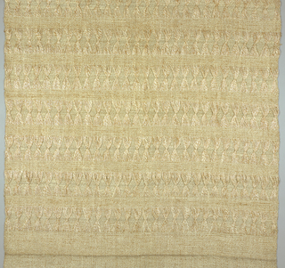 "Length of woven fabric patterned by a regular alternation of bands: 2"" textured band alternating with a 5""band patterned by long warp floats tied in groups forming Xs on a plain weave background.  Yarns are ivory on ivory plied with tan for a total color effect of light tan."