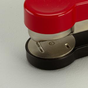 Long rectangular form, hinged at rear, circular terminus at front; red enameled arm, steel magazine; circular steel anvil; black enameled base.