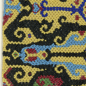 A rectangular panel of yellow, black, red, blue, and green beadwork in geometric hooked pattern.