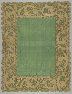 Oblong table cover of dark green silk bordered with green net in an appliqued design of foliage in reversed scrolls that terminate in lilies. Applique is natural colored linen embroidered in dark yellow silk. Edged with natural colored needle lace.