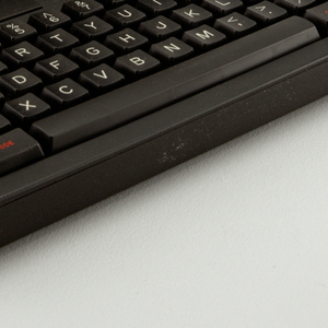 Black rectangular housing, hinged at top center to open, clamshell-style, revealing a wide screen and keyboard.