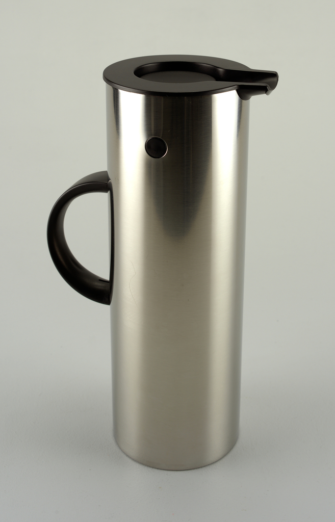 A tall narrow cylindrical red stainless steel thermos with a semicircle handles on side and a small spout off the top in black plastic.