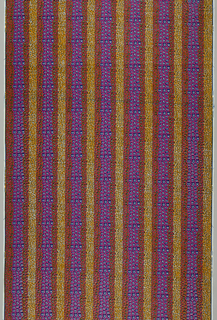 Horizontal bands of irregular spots. Printed in black, blue, and hot pink on a white ground. Snakeskin is the oldest pattern still in the Vlisco line.