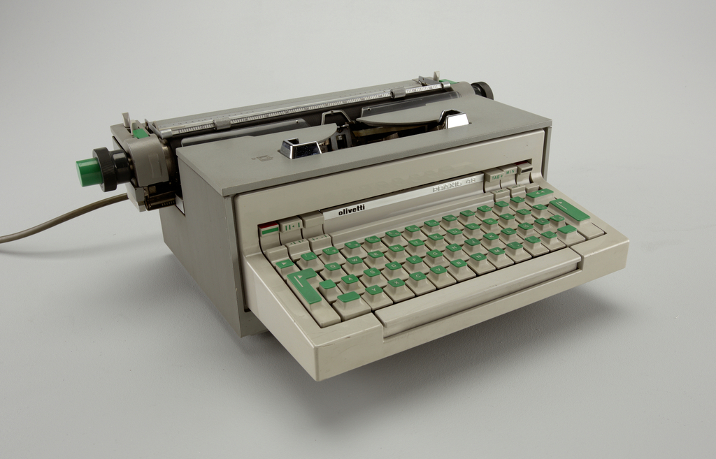 Grey box shaped typewriter with multipurpose keyboard. The top of the keys are green. Lined surface on the left, back and right sides. Mechanical parts on the top also have green details. Black and white ribbon. Removable electric wire in grey.