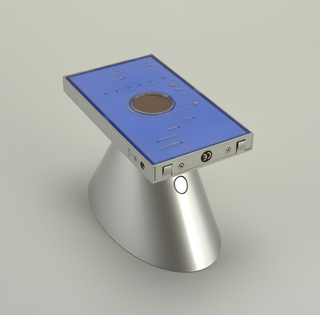Gray conical speaker on its side attached to standing rectangular base with straight telescopic antenna. Text and controls lower right of base.