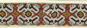 A band with a repeating mirror image animal pattern (frogs?) in beads of white, black, red, blue, green, tan, and pink/purple. It was probably originally a continuous band.