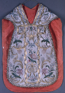Chasuble with vertically symmetrical floral pattern with large gold scrolls.  At center back, an ecclesiastical coat of arms. Gold bobbin lace at edges.