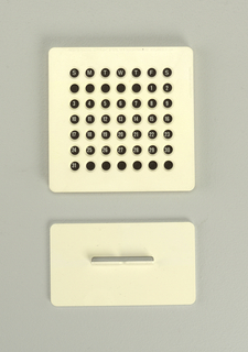 Upright square white plastic form (a) containing card with days of the month and  pierced with rows of circular holes to view dates.  Frame sits on flat rectangular white plastic base (b).