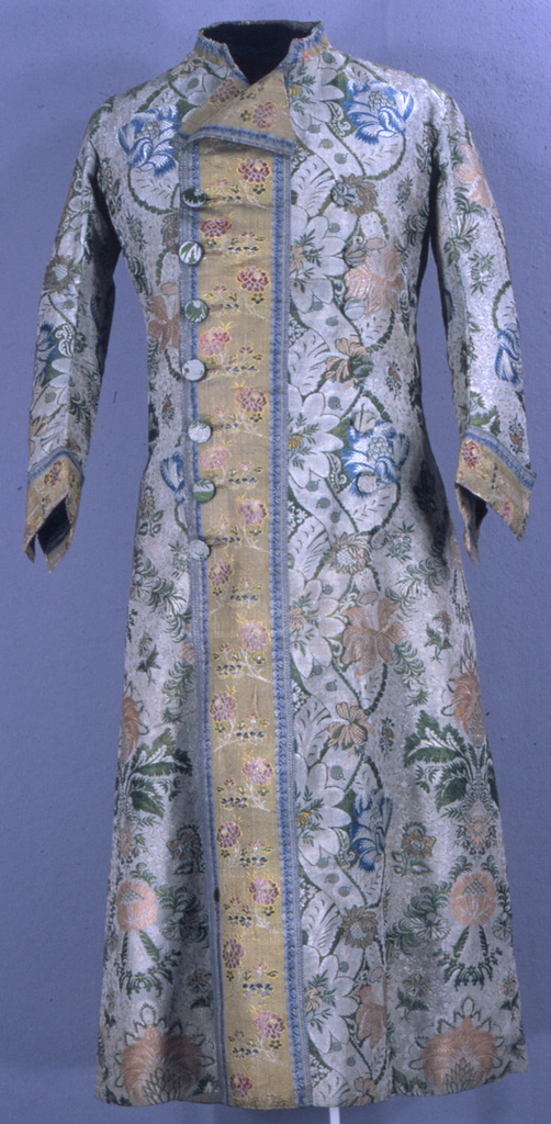 Long, double-breasted man's dressing gown with contrast front edgings, lapels and cuffs.  The robe is of heavy white silk brocaded in the 'bizarre' style with silk chenille showing large-scale florals in blue, green and coral.  The contrasting silk is a pink floral brocade on a yellow ground. Lined with cotton. Buttons of self-material.