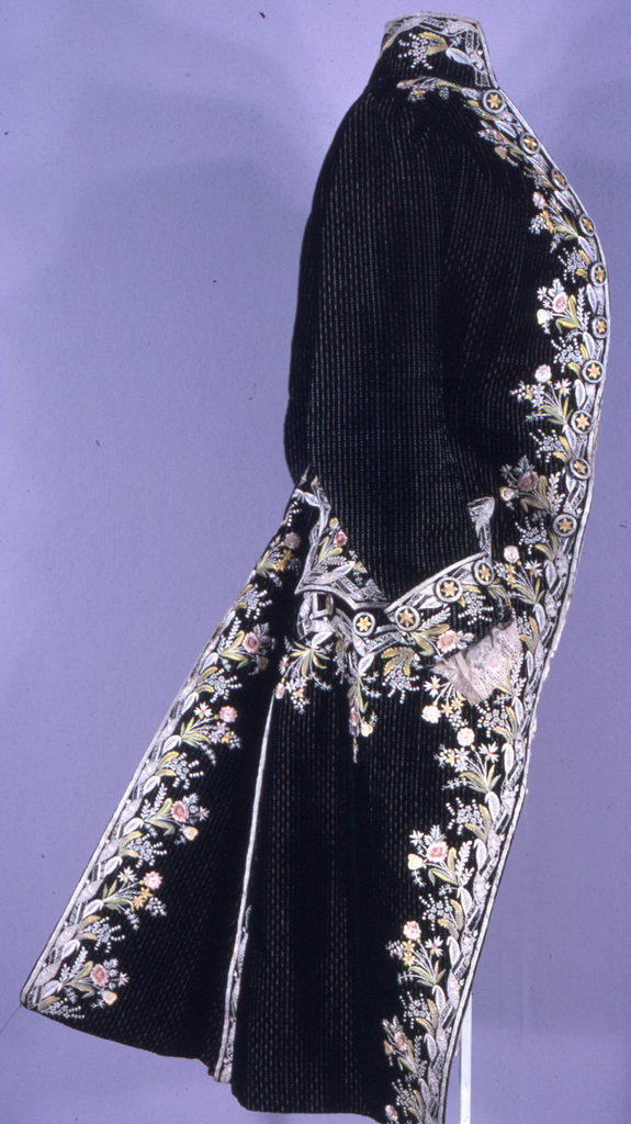 Man's coat, striped black silk cut velvet on silk compound fancy cloth background; collar, cuffs, front and back openings embroidered in floral pattern with polychrome silk; lace (not old) at cuffs; cream-colored satin lining (not original); original satin lining in pockets; embroidery worn.