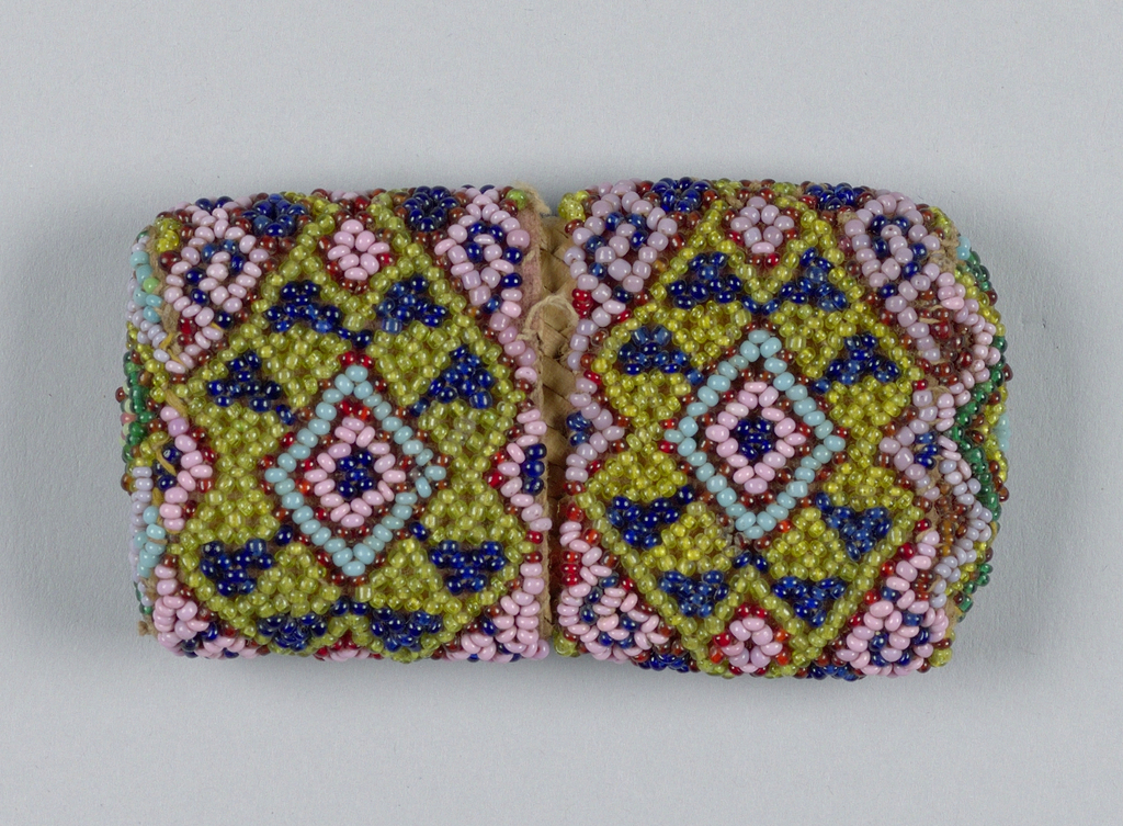 A container with fitted cover, both of interlaced plant material. Strung beadwork of geometrical pattern in green, blue, lavender, and red/brown is attached to the outside.