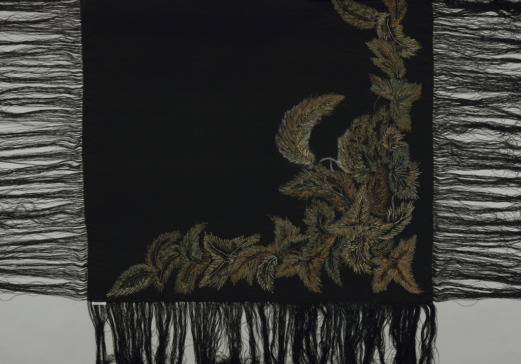 Heavily fringed shawl in multicolor and gold.