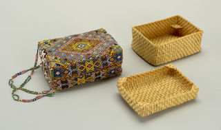 A rectangular box with fitted cover, both of interlaced plant material. The sides and top are covered with red cotton plain weave and then strung beadwork. Within the box are two trays of interlaced plant material--one creating a shelf for the other to rest on. Also holds a smaller box, 1999-5-15. Strung beads connect the top to the box.