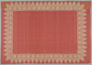 Large reddish-pink table cover with a deeply scalloped lace within the edges of the silk.