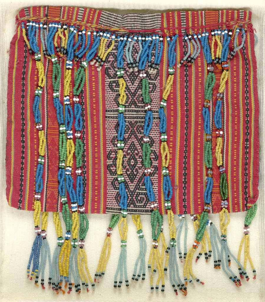 Red woven bag with stripes and geometric pattern in wide middle stripe. Has long fringe of strung beads starting at the opening and hanging past the bottom of the bag in two shades of green, two shades of blue, yellow, white, and black beads.
