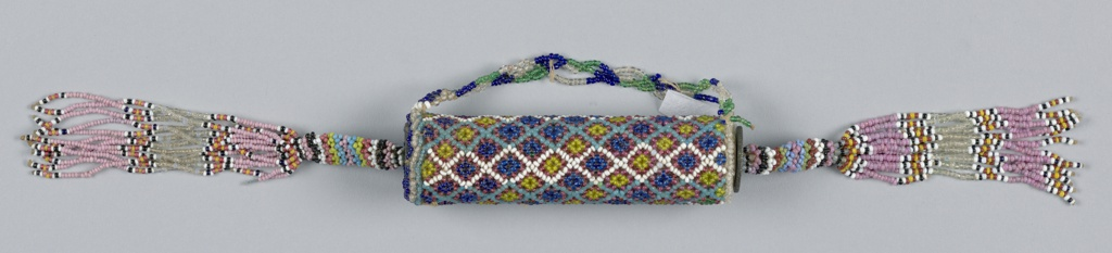 A cylinder covered with strung beadwork in diamond lattice pattern. Both ends are fitted with a European coin and a long beaded tassel; one end has a removeable plug. Purple, yellow, tan, black, blue, white, and green beads