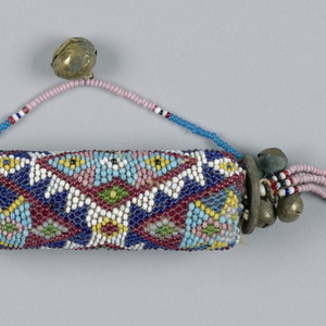A cylinder covered with strung beadwork in geometric pattern. Each end is fitted with large coin, cluster of five bells, and a long beaded tassel. Attached to one tassel is a wooden circle and two small European coins. One end has a removeable plug and strung beads connect that to the cylinder. One bell hangs off of strung beads.
