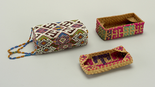 A rectangular box with fitted cover, both of interlaced plant material. The top and sides are covered with red cotton plain weave and then strung beadwork. Within the box are two trays of interlaced plant material--one creating a shelf for the other to rest on. Strung beads connect the cover to the box. Bottom of box features geometric pattern made by dyed woven plant material.