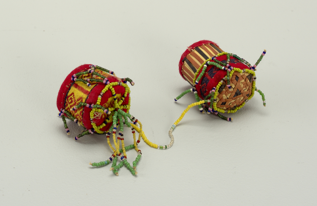 A cylindrical container with fitted cover, both of interlaced plant material. Red plain weave cotton and beadwork cover the sides and bottom of the container. Strung beads connect cover to cylinder. When opened, the outer face of cover's basketry shows dyed plant material arranged in stripe pattern.
