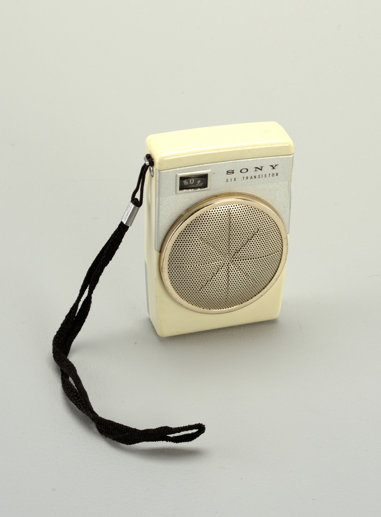 """Small rectangular white plastic body; front with white metal panel with station indicator, """"SONY"""" logo and """"SIX TRANSISTOR,"""" above large, circular, gold-toned pierced metal speaker with recessed asterisk-shaped design; black strap handle on left side; two small white control dials on right side; hinged white metal battery compartment in lower rear."""