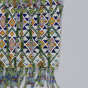 Bag with strung beadwork in geometric pattern. Has long fringe of strung beadwork beginning at opening and hanging past bottom of the bag and a long beadwork handle showing diamond pattern. White, orange, purple, two shades of blue, red, green, black, brown, and pink beads. Lined with plain weave cotton.