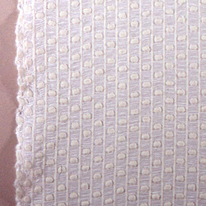 Yardage of full manufactured width, white plain woven wool that form dots and stripes with white rayon pleats in between.