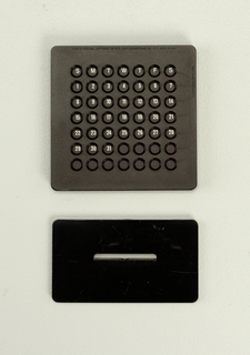 Upright square black plastic form (a) containing card with days of the month and  pierced with rows of circular holes to view dates.  Frame sits on flat rectangular black plastic base (b).