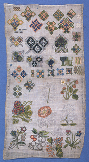 'Random Spot' sampler of geometric figures and isolated floral forms. Selvage at top and bottom of piece.  The unfinished floral motifs at the bottom reveal the outline drawn onto the foundation fabric.