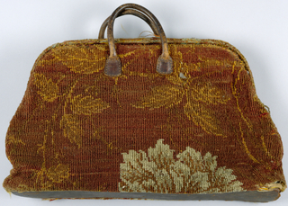 Carpet bag made from Brussels carpet in a large-scale floral pattern in dull red, yellow and off-white.