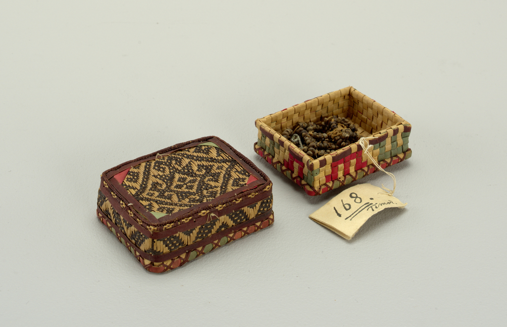 A rectangular box with fitted cover, both of interlaced plant material. The cover also has a pattern of dyed woven plant material. The box contains a string of beads.