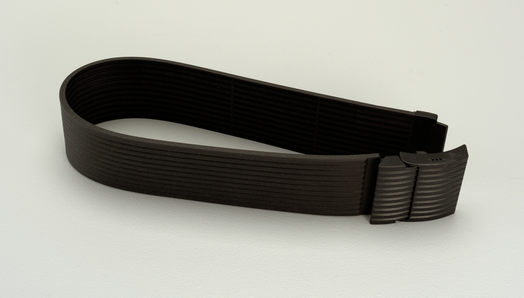 A black plastic belt with horizontal stripes holding together the tool case and the watering can.