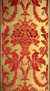 Basket with flowers surrounded by leaf bands, connected by foliate swags. Printed in red flock on ribbed metallic gold ground.