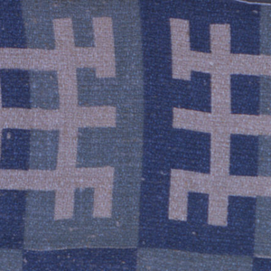 Geometrical motifs composed of block in blue and turquoise on a natural linen ground fabric.