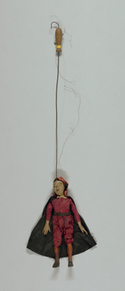Set of Commedia dell'arte marionettes, each with facial masks and costume of stock character. Pantalone shown with bearded mask and hooked nose. Red clothing and cap, black cape. Wooden hands sewn into sleeves.