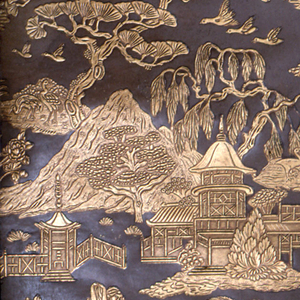 Chinoiserie-style paper, containing motifs of couple walking under a parasol, pagodas, bridges, mountains and trees. Embossed areas printed in gold against a deep brown background.  Same design as 1995-13-4 (Reg. No. 668431).