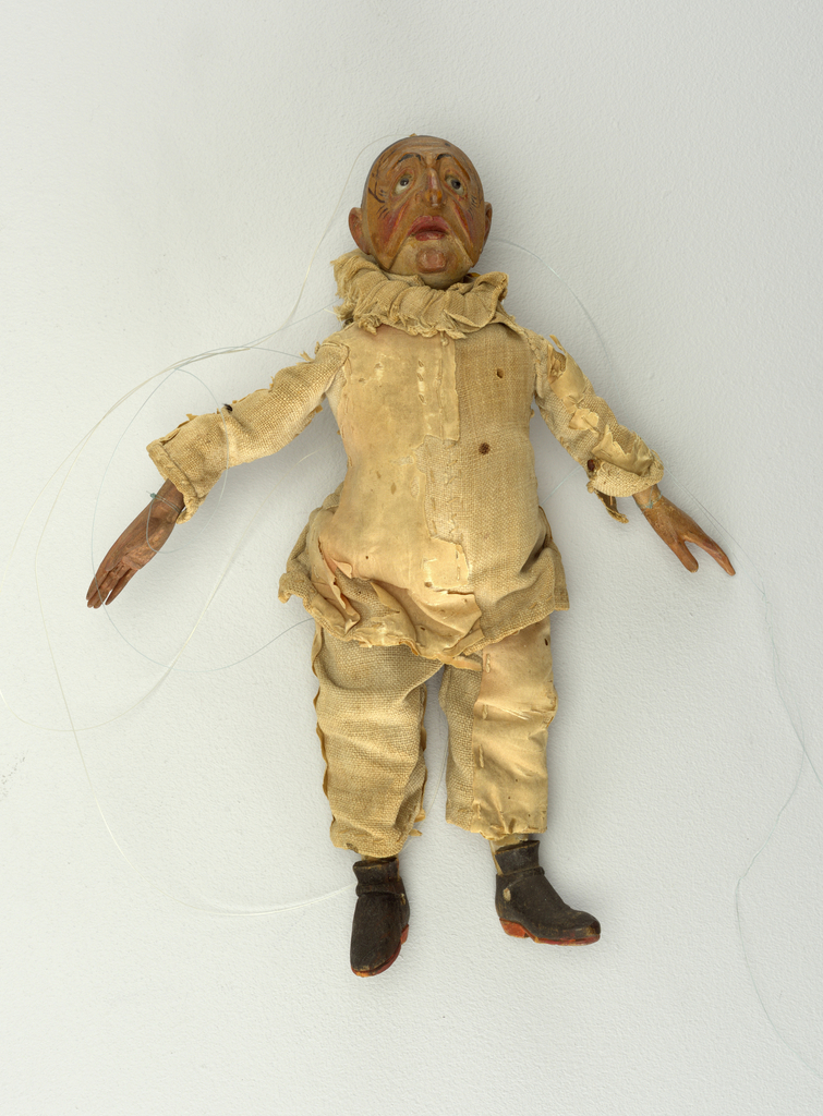 Set of Commedia dell'arte marionettes, each with facial masks and costume of stock character. Pulcinella shown with a drooping mask. White suit with ruffled collar. Black coots. Wooden hands sewn into sleeves.