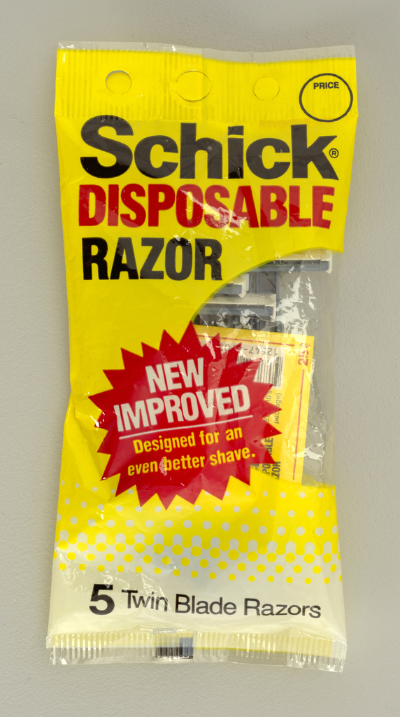"""Two packages of razors: the first made by Gillette called the """"micro track"""", labeled across the top front in black print. The light brown plastic packaging also has a diagonal yellow label across the front saying """"2 Free"""".  Below that a circle with an image of the razor. The blade of the razor is covered with a price sticker saying """".88"""". At the bottom right corner there is a black crossed out """"5"""" with a red """"7"""" next to it.  The second package is a slightly smaller yellow rectangle package. Across the top in black and red, the package is labels """"Schick Disposable Razors"""". Below there is a """"New and Improved"""" circular label with a clear plastic window to the right exposing the blue razors within."""