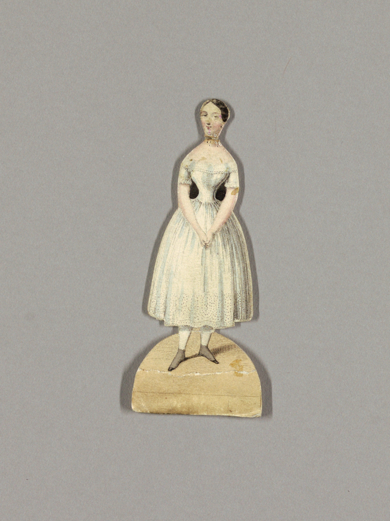Female paper doll with a small oval face and straight dark brown hair that is pulled back in a circular bun and held in place with a gold comb.  The doll is dressed in a petticoat, appropriate for the time period.