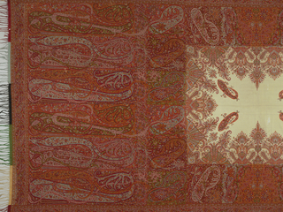 Paisley shawl with deep borders in shades of red, orange, blue, and white. Shawl ends have a row of tall paisleys with an inner border of small paisley motifs. White center field has small paisleys, scrolling bands and floral clusters.