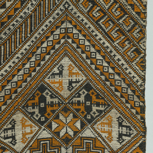 Geometric patterns woven in dark blue cotton, white cotton and orange silk. Warp end cut at one end and hemmed at the other