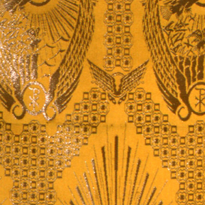 Section of a golden yellow fancy satin with large diagonal repeat in gold metal of long ovals with eagles against a rayed sun framed in a pair of long pointed wings rising from circles containing monogram of Christ; diapered trellis framework. Two wide plain cloth selvages.
