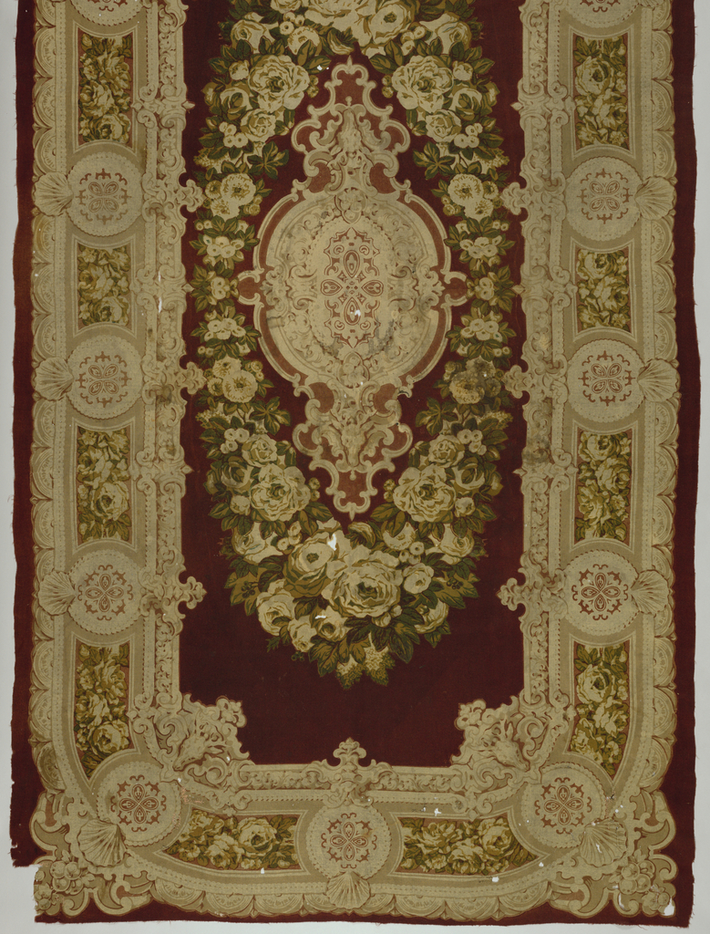 Printed wool rectangular table cover. Field: medallion surrounded by a wreath of flowers on maroon field. Border: elaborately edged repeat of floral band and medallion which round the corners. Note stag head on inside border at corners. Dark somber colors.