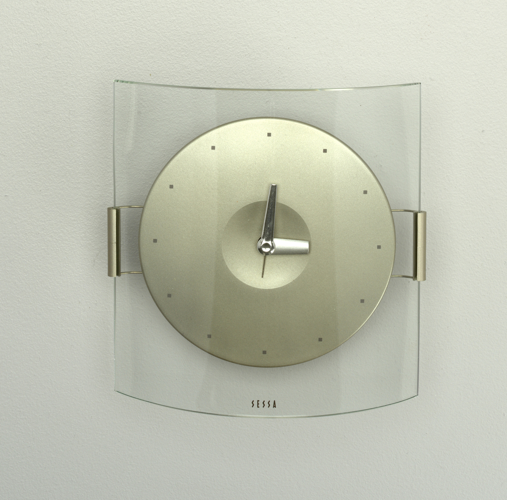 Circular clock face of white metal with 12 dots as numbers; suspended in convex clear glass stand; white metal hour hand, black minute hand, yellow second hand.