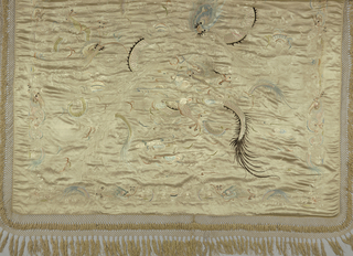 Cream-colored panel embroidered with pastel silks and touches of black with large central design of big and small dragons with flaming pearl and fish in delicate cloud and water conventions. Enclosing border set in from edge of smaller dragons, lotus, and flaming pearl. Deep knotted tan silk fringe. Lined with pongee.