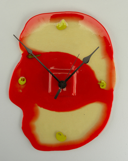 Flat, irregularly shaped resin wall clock, red at edges and through center; smudge-like green dots at the 12, 3, 6, 9, and 10 positions;  slim black metal hands.