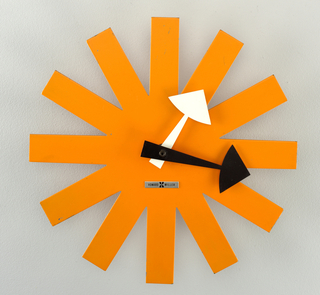 Clock with a body in the shape of an asterisk with one white and one black hand in the shape of arrows.
