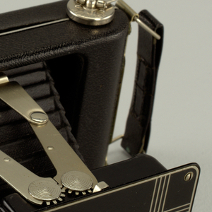 Medium format folding camera with painted front plate and carrying strap at top; survives with original packaging